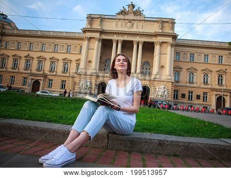 Pensive student girl in a city park with a book on the background of a university building