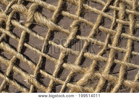 Closeup loosely woven net made of natural rope fibers lying over wood in sun with strong shadows