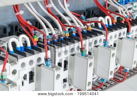 The number of contactors arranged in a row in an electrical closet. The contactors connected wire number coded. Contactors with front auxiliary contacts. The wires go into perforated cable channels.