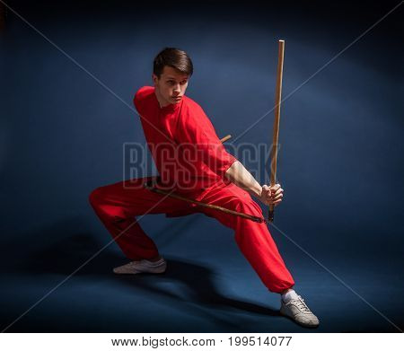 Boy in a red kimono engaged wushu against a dark background