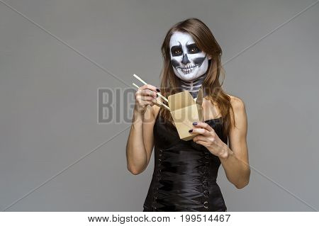 Young beautiful girl with a sugar skull make up holds in her hand a paper box for instant noodles and chopsticks. Halloween face art on gray background.