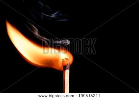 Lone Burning Match With The Flame In The Upper Left Side Of The Frame Isolated On Black Background