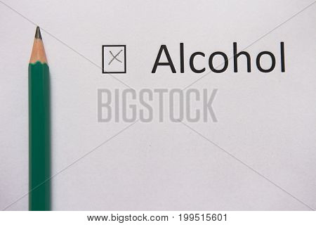 Stop drinking. word ALCOHOL is written on white paper with cross and gray pencil.