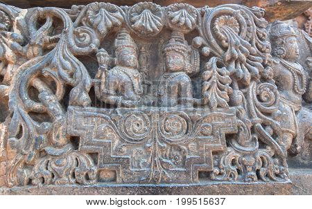 Two Hindu gods in carved royal cart. Lord Shiva and his wife Parvati on sculptured wall of 12th centur Hindu Hoysaleshwara temple in Halebidu, India.