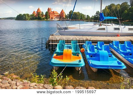 Catamarans against backdrop of Trakai castle in Lithuania on bright summer day. Tourism in the Trakai Castle