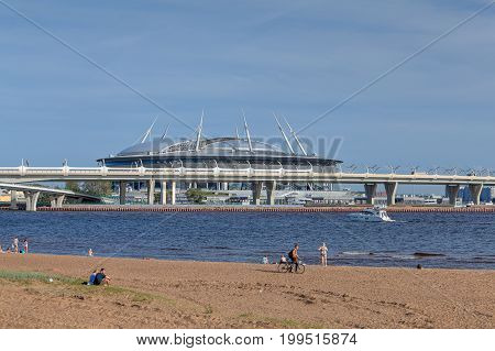 St. Petersburg Russia - August 1 2017: Park 300th anniversary of Saint Petersburg сity sandy beach on a sunny summer day townsfolk rest near the water in background of football stadium Zenit Arena