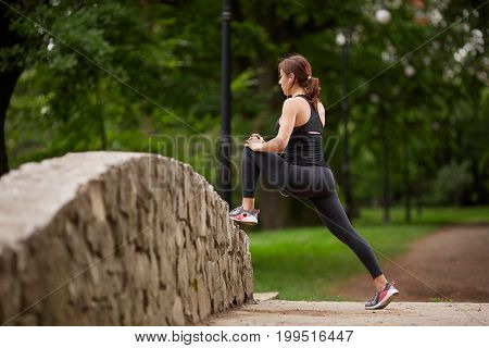 Anonymous woman stretching legs in park looking forward. Fitness woman. Fitness woman in the city park. Caucasian female fitness model working out in the morning