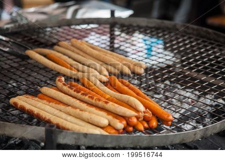 cooking sausages on the grill in a street cafe