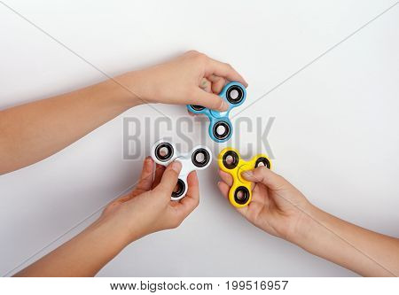 Three hands showing fidget spinners in different colors