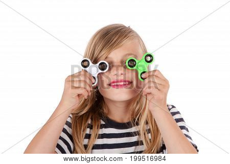 Portrait of a girl playing with two fidget spinners. Isolated on white background.