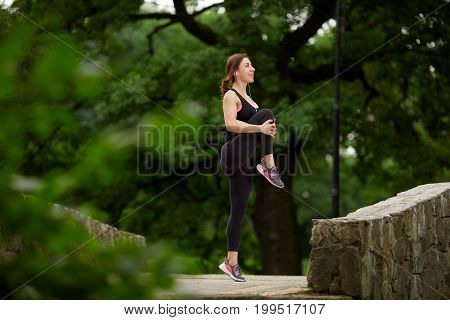 Side view of smiling sportswoman listening to music and stretching legs park. Fitness woman. Fitness woman in the city park. Caucasian female fitness model working out in the morning