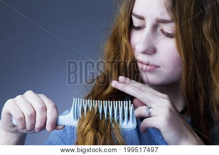 Portrait of a stressed young woman with tousled and disheveled long hair want to comb her hair