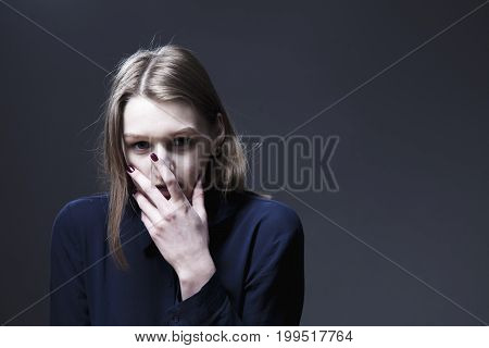 Young sad and desperate woman suffering from a severe depression anxiety sudden fear (Body language gestures facial expressions psychology concepts)