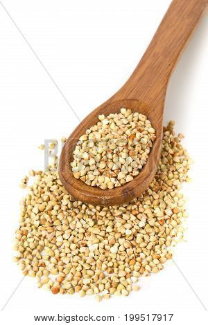Raw natural uncooked buckwheat seed kernels in wooden spoon over white background