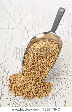 Raw natural uncooked buckwheat seed kernels in metal scoop on rustic white table background
