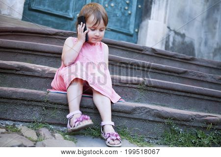 Telephone conversation. Beautiful child girl speaking on the phone in the ancient European city.
