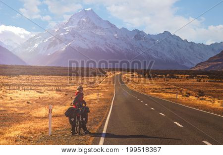 Woman on a cycle touring trip on a road leading to the Mount Cook, highest peak in New Zealand