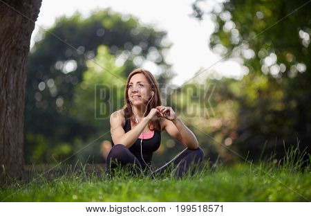 Young cheerful girl in sportswear using headphones and looking happily away on green grass. Fitness woman. Fitness woman in the city park. Caucasian female fitness model working out in the morning