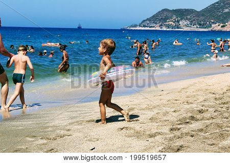 July, 2017 - A child with an inflatable circle runs along the beach to the water at Cleopatra Beach (Alanya, Turkey).