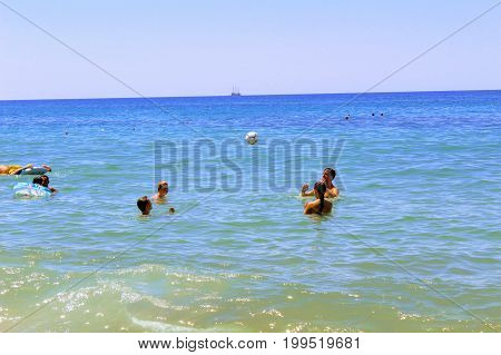 July, 2017 - A group of young people playing ball in the water at Cleopatra Beach (Alanya, Turkey).