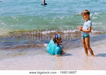 July, 2017 - A man in a scuba mask talks to a young son at Cleopatra Beach (Alanya, Turkey).
