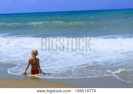 July, 2017 - A woman in a red swimsuit in the surf on the seashore at Cleopatra Beach (Alanya, Turkey).