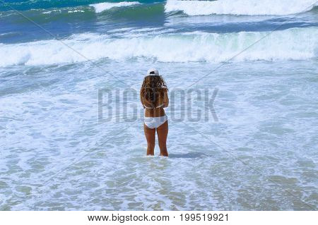 July, 2017 - A lonely woman stands in the surf band on Cleopatra Beach (Alanya, Turkey).