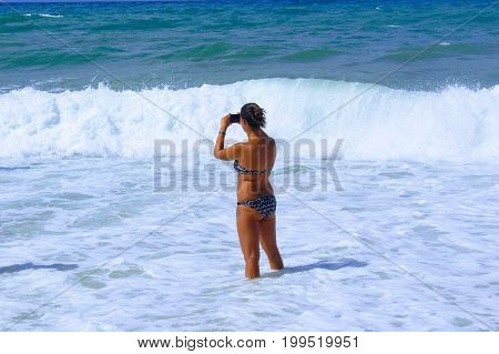 July, 2017 - A young girl makes a photo standing in the surf band on Cleopatra Beach (Alanya, Turkey).