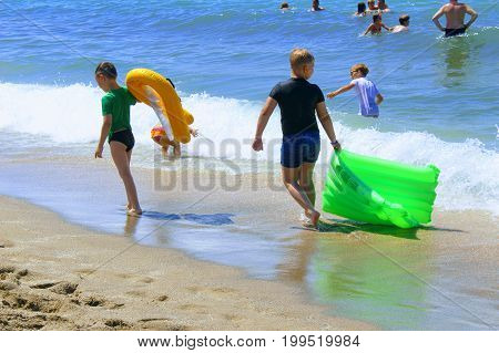 July, 2017 - Children with inflatable mattresses go along the beach to Cleopatra Beach (Alanya, Turkey).
