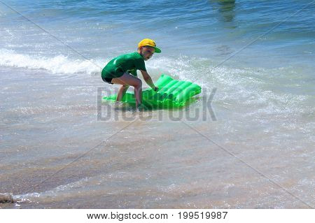 July, 2017 - A boy in a yellow cap with an inflatable green mattress bathes in the surf band at Cleopatra Beach (Alanya, Turkey).