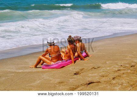 July, 2017 - Three tanned women sunbathe on a pink mattress sitting on the seashore at Cleopatra Beach (Alanya, Turkey).