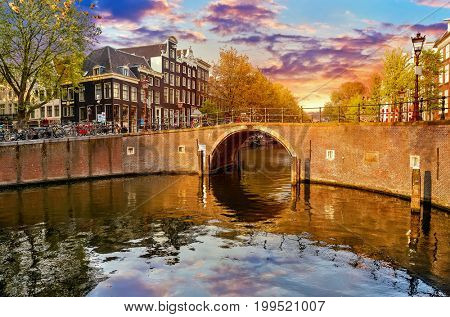 Channel in Amsterdam Netherlands Holland houses under river Amstel. Landmark old european city spring landscape with sunshine.