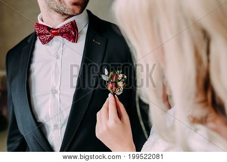 Wedding. Close Up Bride's Hands Pinning Boutonniere To Groom' Jacket. Soft Focus On Boutonniere