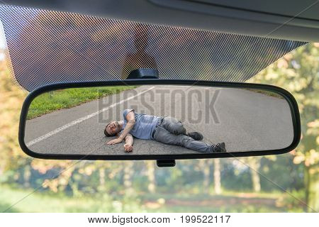 Hit And Run Concept. View On Injured Man On Road In Rear Mirror