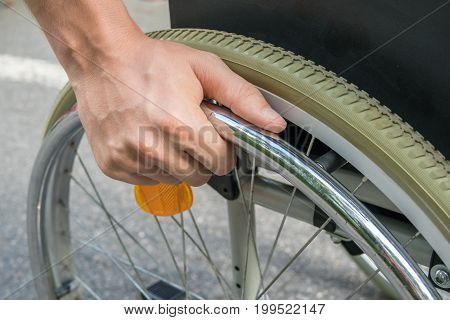 Close up view on hand of handicapped man on wheelchair.