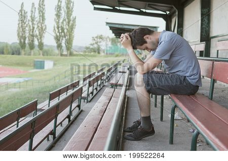 Despair And Depressed Man Is Sitting In Stadium. Solitary And Lo