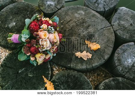 Wedding Bouquet Of Color Marsala Lies On A Wooden Background. Beautiful Flower Bunch With White And