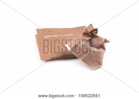 Intact and crumpled packaging of brown sugar. Isolated white background. Concept of cutting down sugar intake.