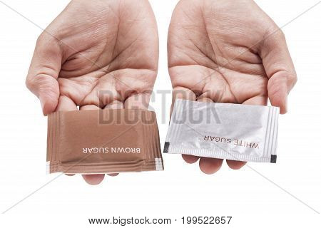 Hands serving brown and white sugar pack. Isolated white background.