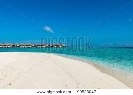 Wide angle picture of turquoise water with bungalows during a sunny day in Maldives