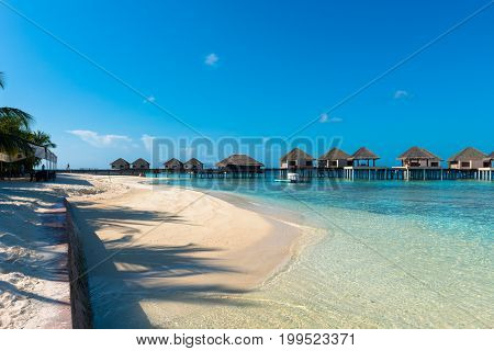 Horizontal picture of turquoise water with white sand beach with some bungalows during a sunny day in Maldives
