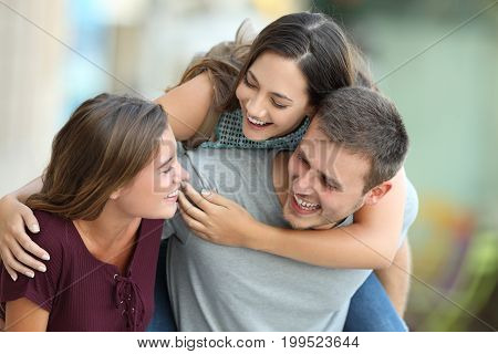 Three happy friends meeting and joking together on the street