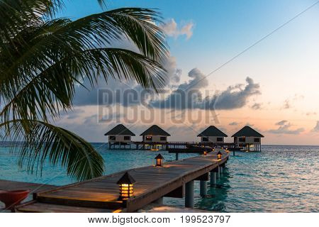 Wide angle picture of wooden way to go to the rooms on top of turquoise water in a island close to Maafushi in Maldives at sunset time.