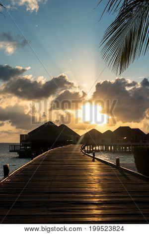 Vertical picture of yellow beautiful sunset over bungalows with cloudy sky in Maldives.