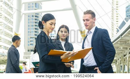 team of business people smart man and woman talk about the project and business work and see on the paper file book in feeling smile and happy with the city space background and people worker in the outdoor morning sky