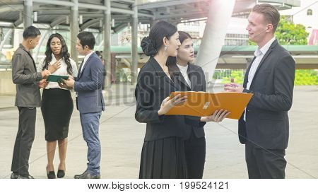 team of business people smart man and woman talk about the project and business work and see on the paper file book in feeling smile and happy with the city space background in the outdoor morning sky