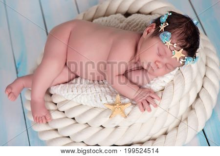 Close portrait of a sleeping newborn girl in the maritime hoop of starfish and pearls.