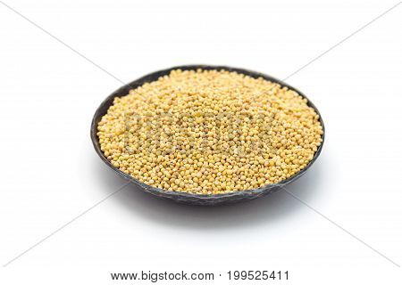 Organic millet groats in a metal bowl side view isolated