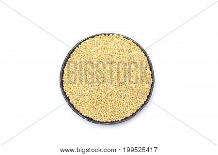 Organic millet groats in a metal bowl top view isolated
