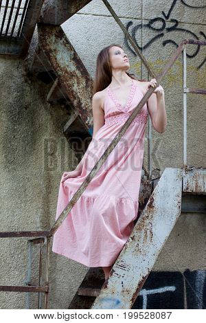 Young Girl Standing On Old Stairs